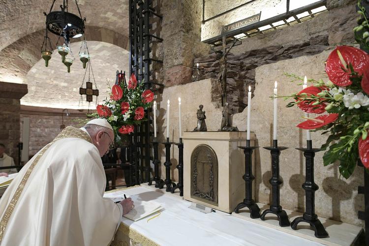 """Le Saint Père en train de signer sa nouvelle encyclique """"Fratelli Tutti, fraternité et amitié sociale"""" après avoir célébré la messes dans la basilique Saint-François, à Assise, en Italie le 3 oct 2020"""